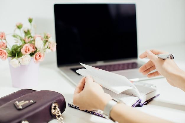 Mão de mulher escrevendo no bloco de notas vazio colocado na área de trabalho do escritório com laptop, vaso de flores