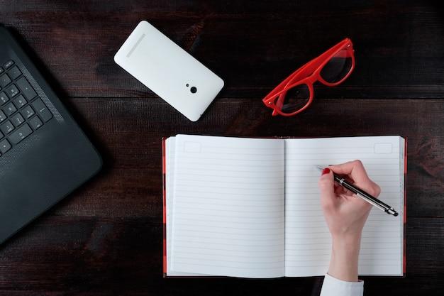 Mão de mulher escrevendo no caderno, conjunto de negócios de laptop óculos smartphone vista superior