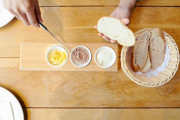 Mão de mulher espalhar manteiga no pão fatiado