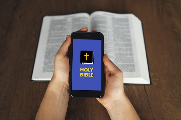 Mão de mulher espera e telefone inteligente de tela de toque, celular na igreja sobre o livro sagrado e etário da bíblia turva.