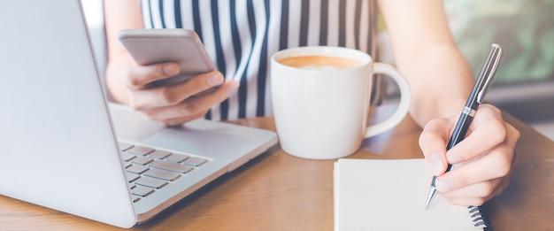 Mão de mulher está escrevendo um caderno e usando um telefone no escritório.