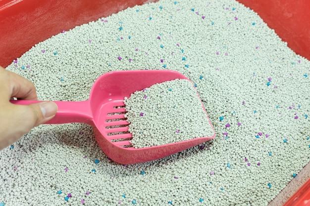 Mão de mulher está limpando a caixa de areia do gato com uma colher rosa
