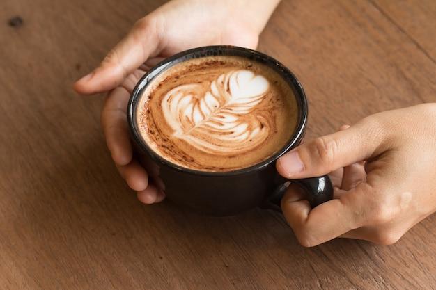Mão de mulher está segurando piccolo latte art em um copo no topo lindo coração