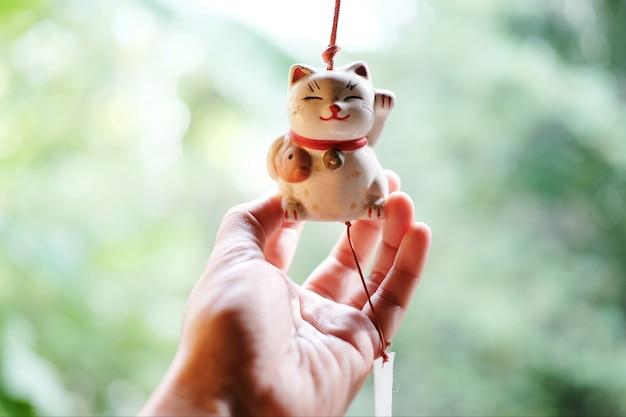 Mão de mulher está segurando uma boneca de gato sorte do japão