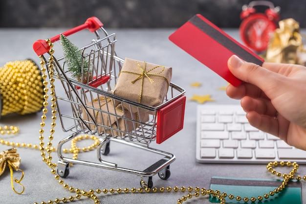 Mão de mulher está tomando cartão de crédito perto de pequeno carrinho de compras vermelho com teclado