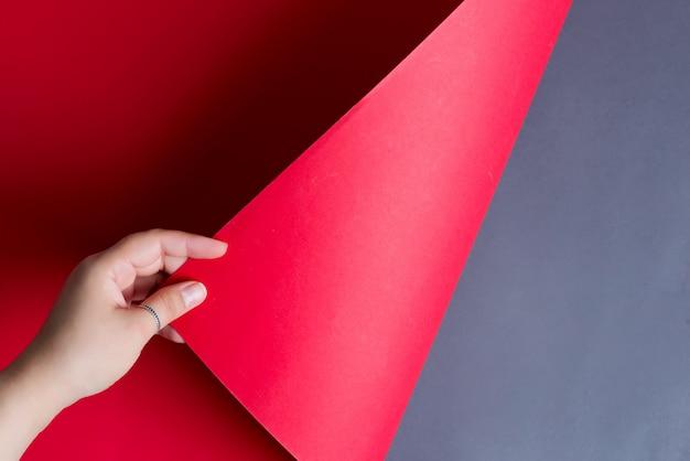 Mão de mulher está virando a folha de papel vermelho sobre um fundo preto com sombras suaves.