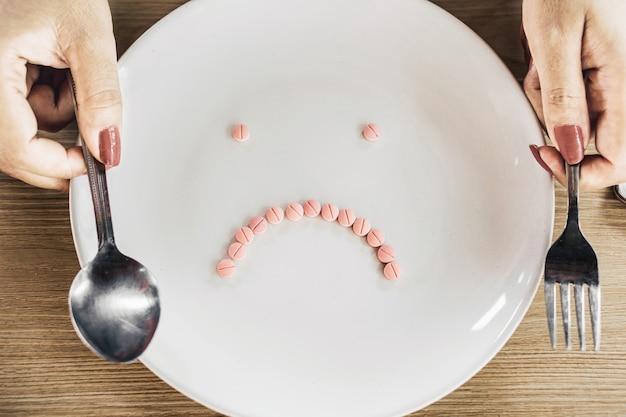 Mão de mulher falando comprimidos de dieta no prato