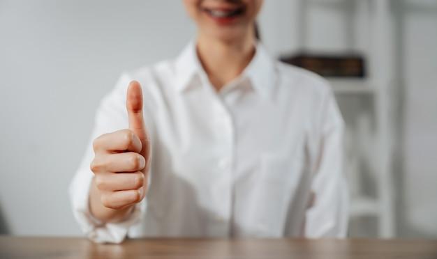 Mão de mulher fazendo o polegar para cima o sinal e sorrindo na mesa.