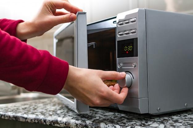 Mão de mulher, fechando a porta do forno de microondas e define o tempo para aquecer os alimentos