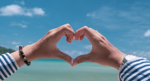 Mão de mulher forma de coração no céu azul e fundo da praia.