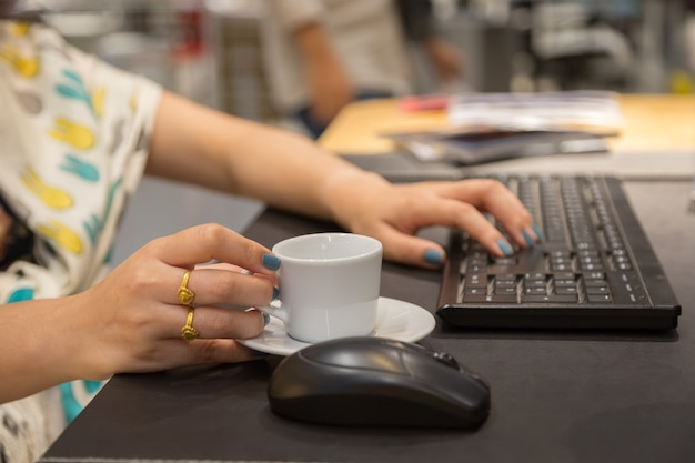 Mão de mulher holdding xícara de café com fundo de mesa de trabalho
