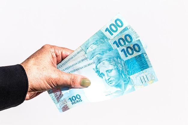 Mão de mulher idosa segurando notas de dinheiro do brasil, cem reais com superfície branca isolada