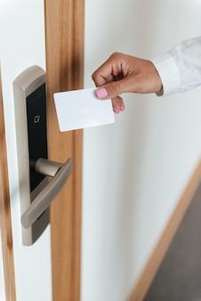 Mão de mulher, inserção de cartão-chave na fechadura eletrônica