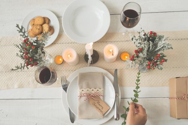 Mão de mulher irreconhecível, colocando o ramo verde na mesa de jantar de natal