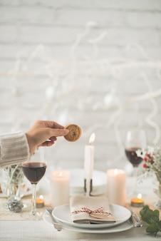 Mão de mulher irreconhecível, segurando o biscoito acima da mesa de jantar de natal