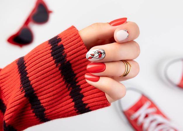 Mão de mulher jovem bonita com manicure vermelha em cinza