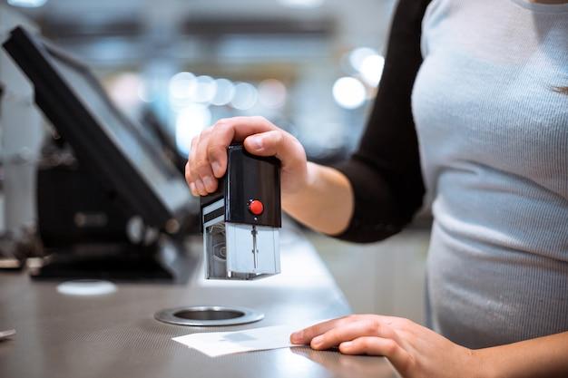 Mão de mulher jovem fazendo o pagamento do processo, obtendo o selo com a venda de um recibo no enorme shopping center, conceito de finanças