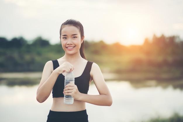 Mão de mulher jovem fitness segurando a garrafa de água após a execução do exercício