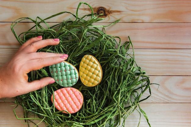 Mão de mulher leva um dos cookies de ovos de páscoa coloridos do ninho na luz de fundo de madeira