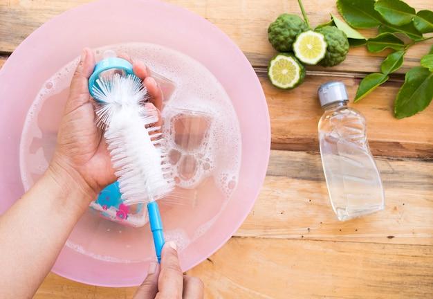 Mão de mulher limpando mamadeiras de bebê com líquido de limpeza