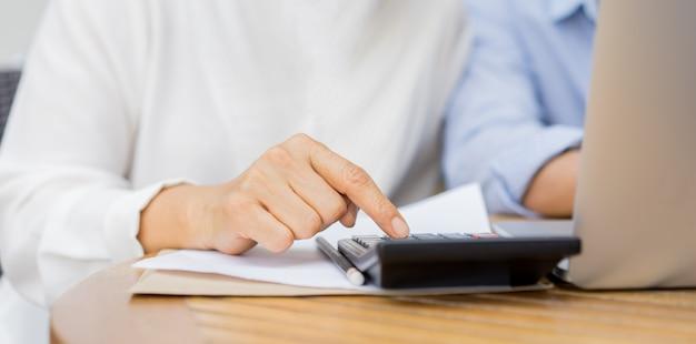 Mão de mulher madura, pressionando a calculadora para calcular as despesas mensais