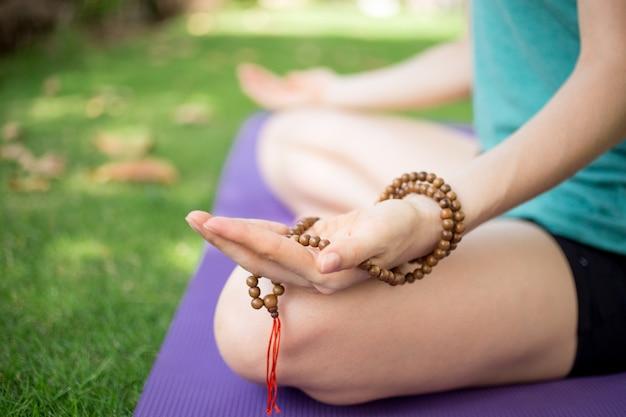 Mão de mulher meditando segurando rosários