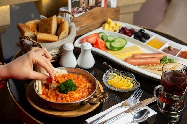 Mão de mulher, mergulhando o pão no prato de ovo e tomate, servido para a instalação do café da manhã