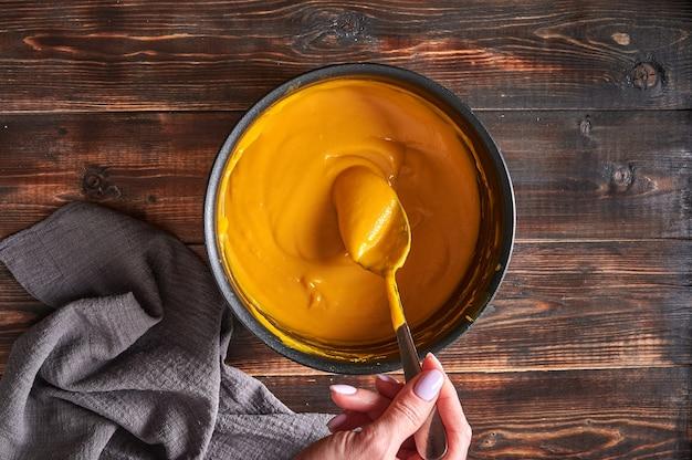 Mão de mulher mexendo com colher sopa de creme de purê de abóbora tradicional em uma panela sobre tábuas de madeira