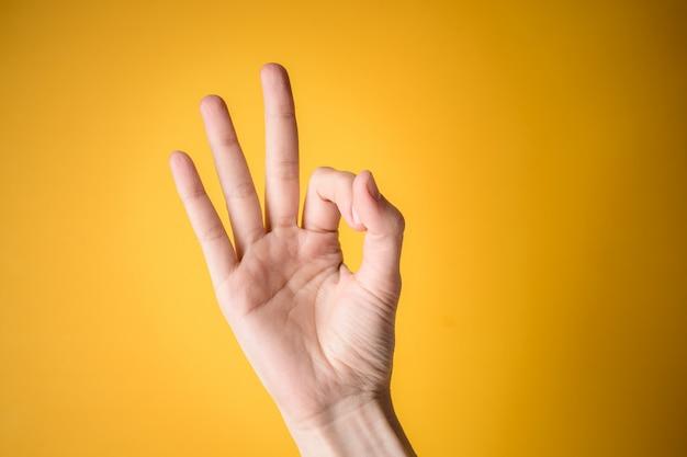 Mão de mulher mostra gesto bem em fundo amarelo