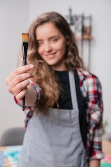 Mão de mulher mostrando pincel não utilizado preto