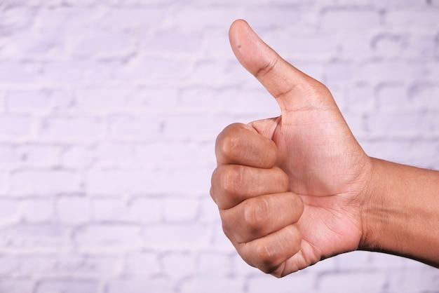 Mão de mulher mostrando um polegar para cima na parede branca