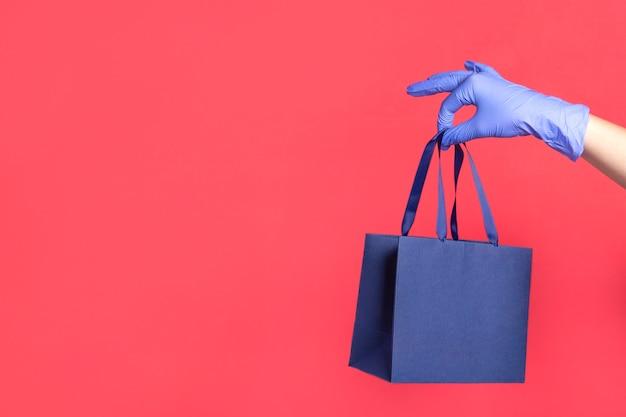 Mão de mulher na luva com saco de papel de presente na superfície vermelha