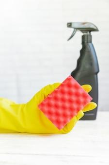 Mão de mulher na luva de borracha amarela, segurando a esponja de limpeza. . produto de limpeza.
