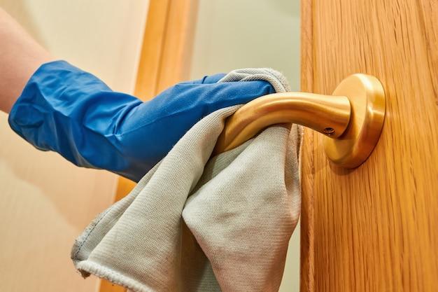 Mão de mulher na luva protetora azul usando desinfetante e pano de limpeza para limpar a maçaneta de vírus. closeup, foco seletivo