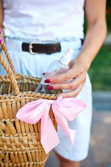 Mão de mulher na moda com bolsa de palha e gel desinfetante para as mãos na bolsa