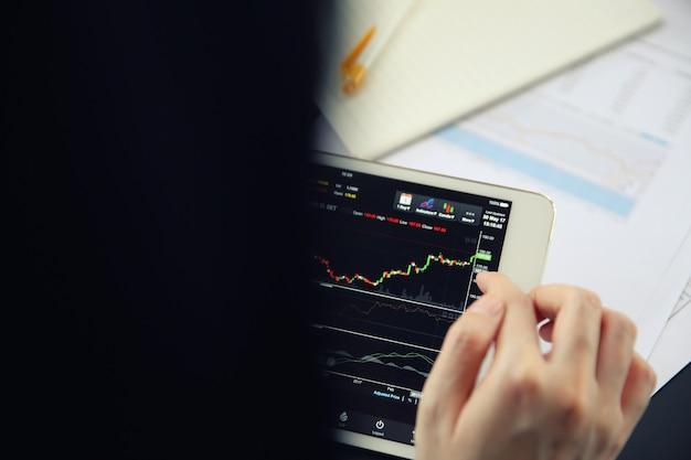 Mão de mulher negociação on-line no tablet com papel de negócios e café
