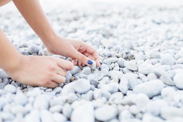 Mão de mulher pegando seixos na praia