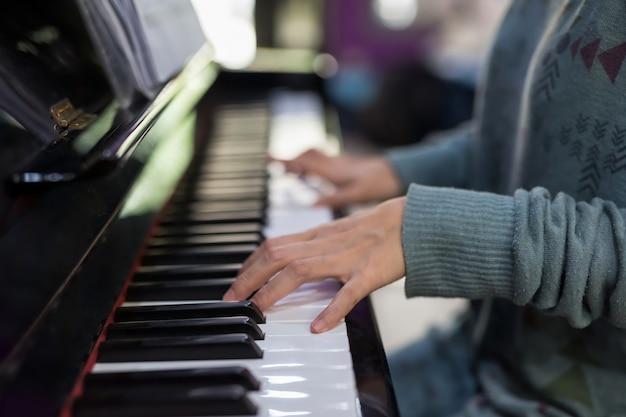 Mão de mulher pianista tocando no teclado de piano clássico