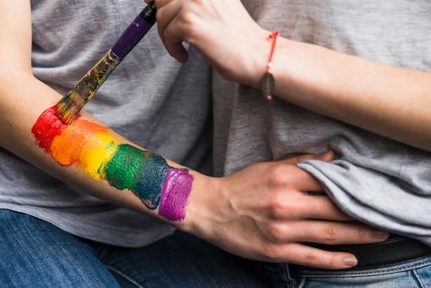 Mão de mulher pintando a bandeira do arco-íris sobre a mão da namorada com pincel