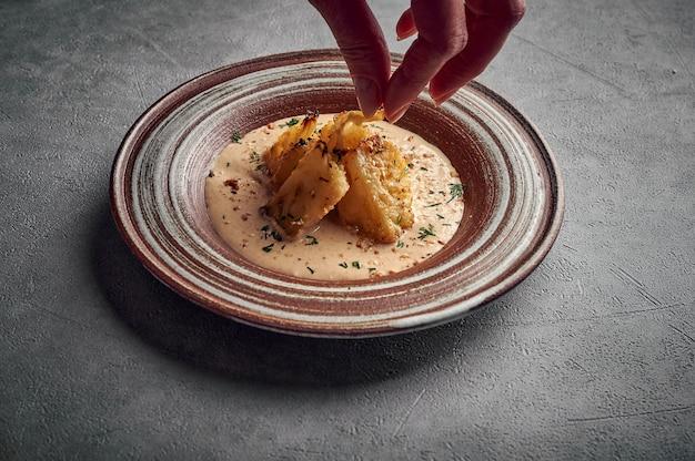 Mão de mulher polvilhada com couve-flor caseira assada com endro ao molho de queijo gruyere e azeite no prato escuro