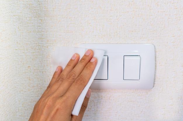 Mão de mulher que limpa o interruptor da luz com limpeza molhada desinfetante no quarto em casa. conceito de desinfecção de superfícies e item de uso diário de bactérias ou vírus. fechar-se.