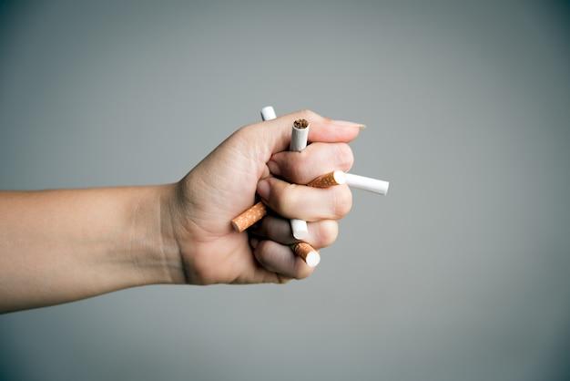 Mão de mulher quebrando cigarros. dia mundial sem tabaco