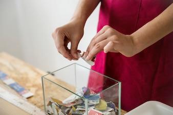 Mão de mulher rasgando papel em pedaços