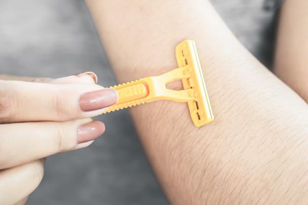 Mão de mulher raspando os braços do cabelo