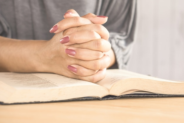 Mão de mulher rezando na igreja com o livro da bíblia