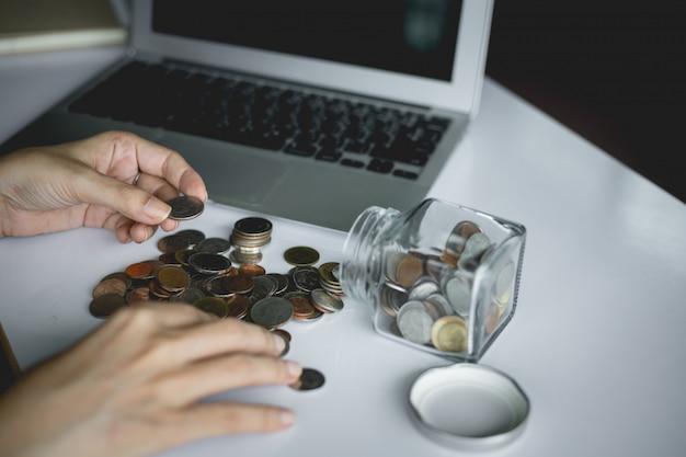 Mão de mulher, salvando e contando moedas de dinheiro no pote de vidro com o computador portátil para o conceito de planejamento, negócios e finanças