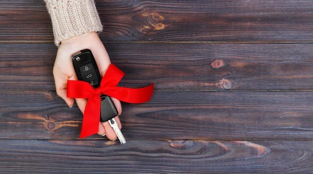 Mão de mulher segura a chave do carro com laço vermelho. dar um carro como presente banner