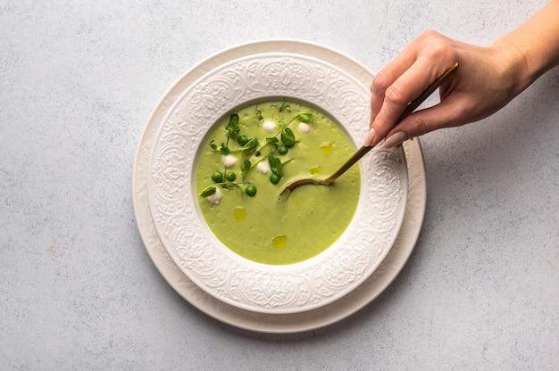 Mão de mulher segura a colher de sopa de purê de ervilhas verdes, leite de coco com mini queijo mussarela em