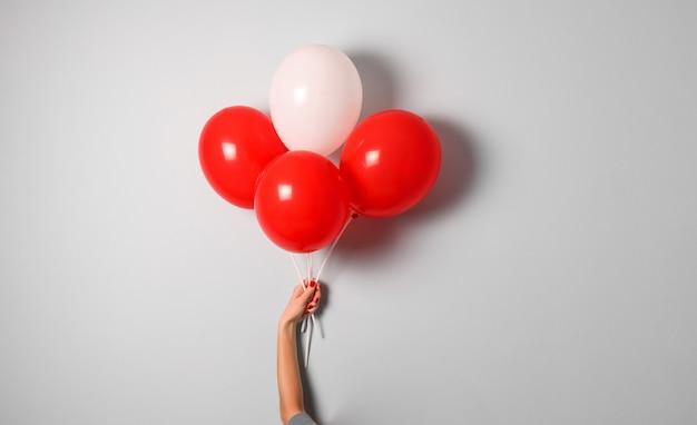 Mão de mulher segura balão de ar vermelho e branco