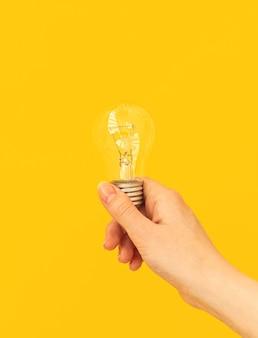 Mão de mulher segura lâmpada apagada em fundo irange ou amarelo, foto do conceito de ideia